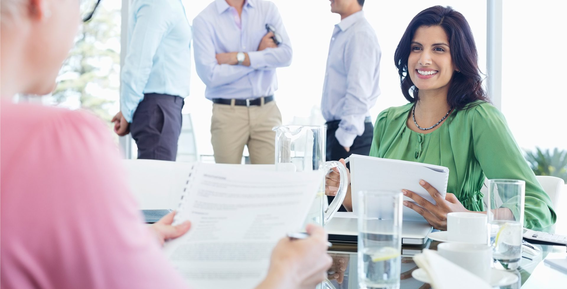 woman working at conference table drinking refreshing water
