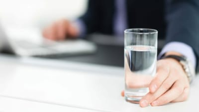 business man drinking a glass of water from reverses osmosis filtration