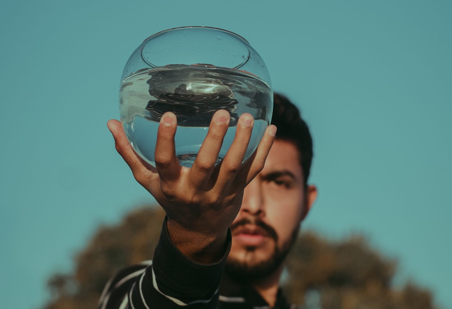 man holding large round glass of water outside