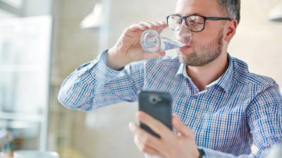 man drinking water while looking at water tracker apps