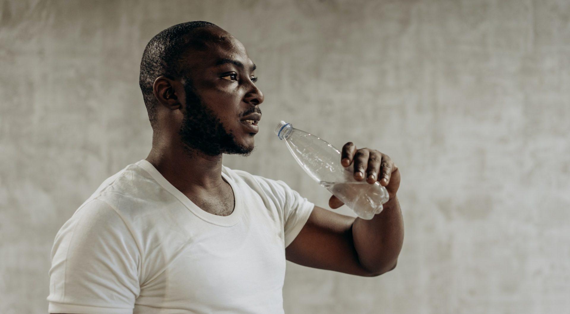 man drinking water from a bottle with a white t shirt on