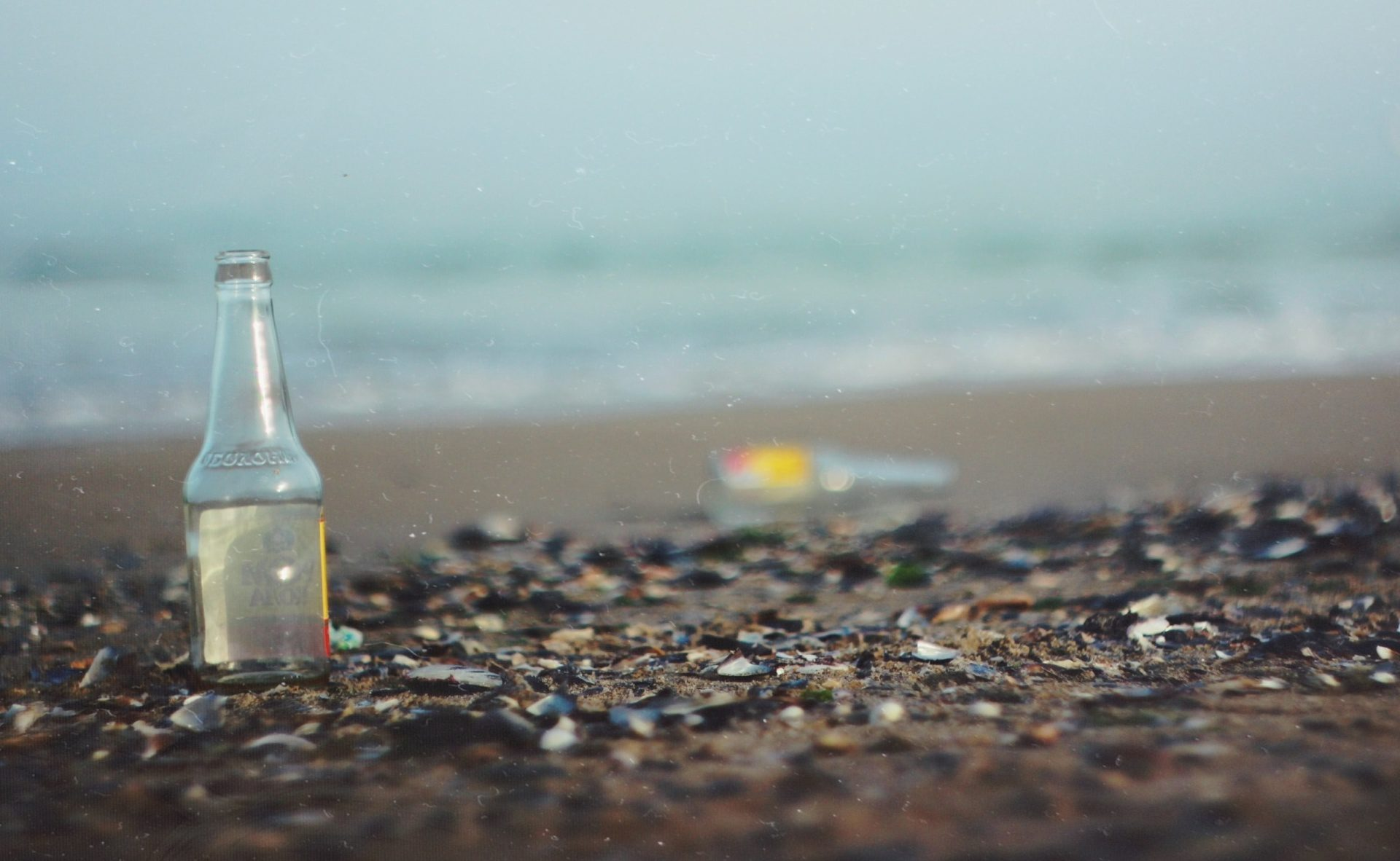 glass littered on the beach on a gloomy day
