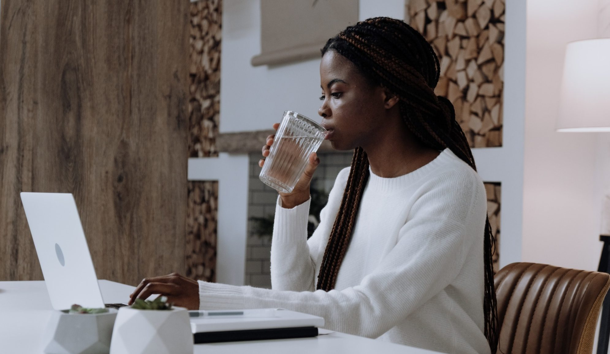 black woman drinking water and working on laptop