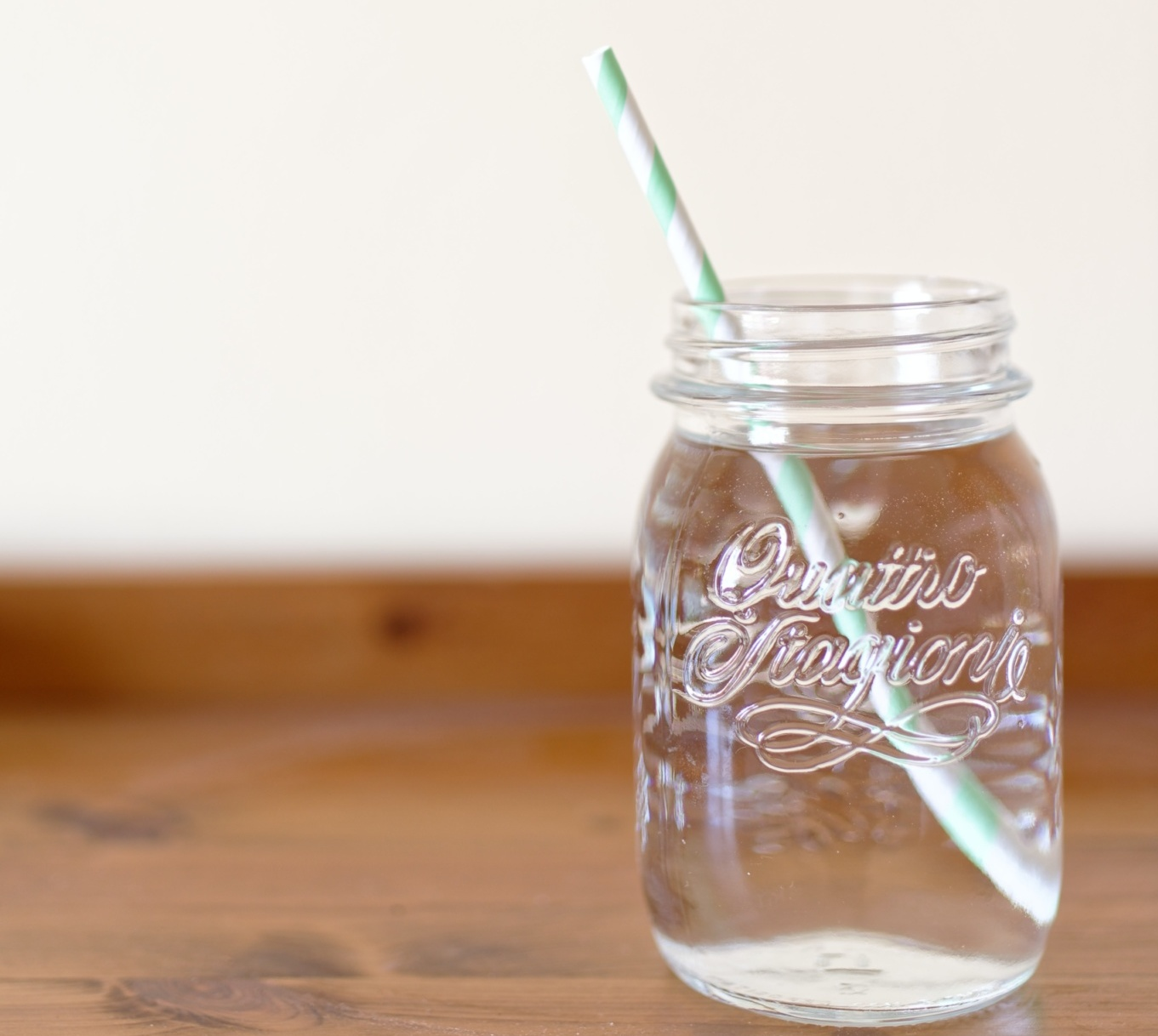 jar of water with straw in it sitting on wooden table