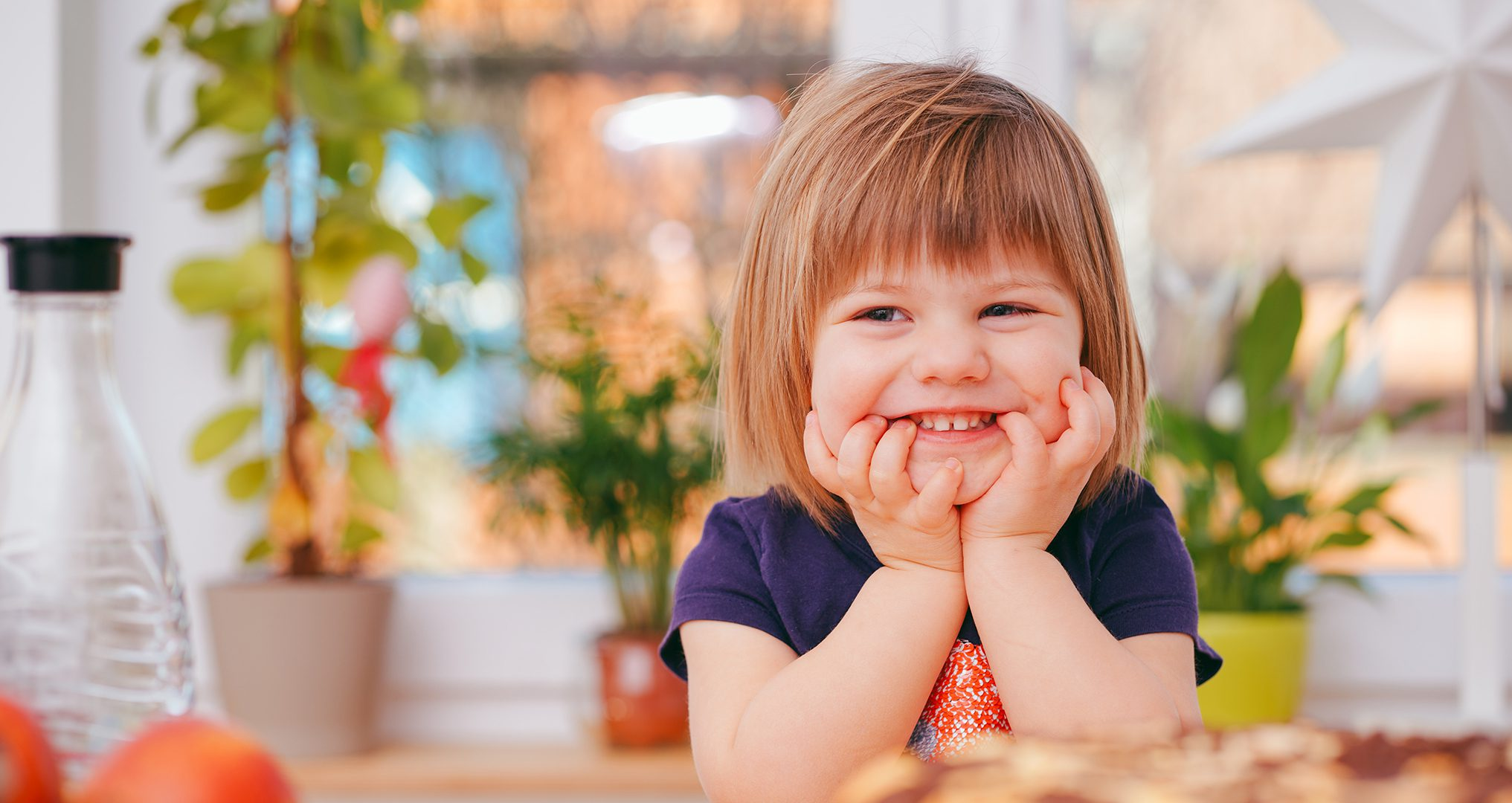 Child smiling at table waiting for water by Optimum