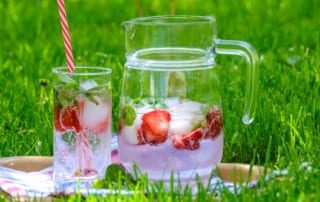 pitcher and glass of water with fruit