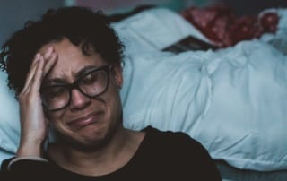 woman sitting beside bed crying with her hand on her head