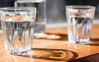 three glasses of water sitting on a table