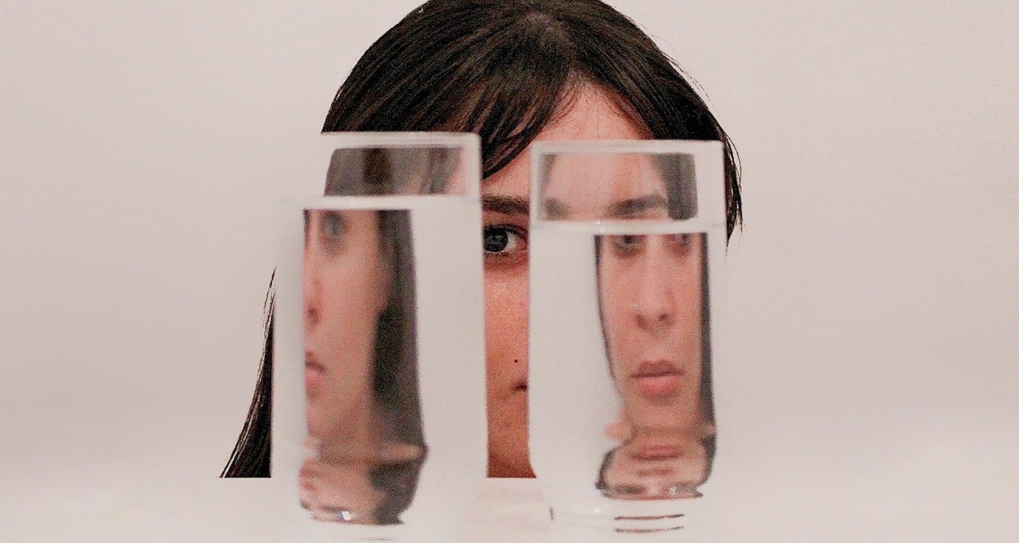 woman looking through two side by side glasses of water