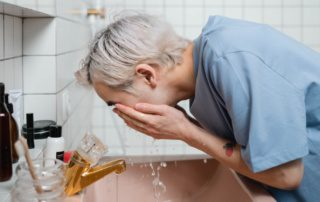 man washing is face over the sink in bathroom