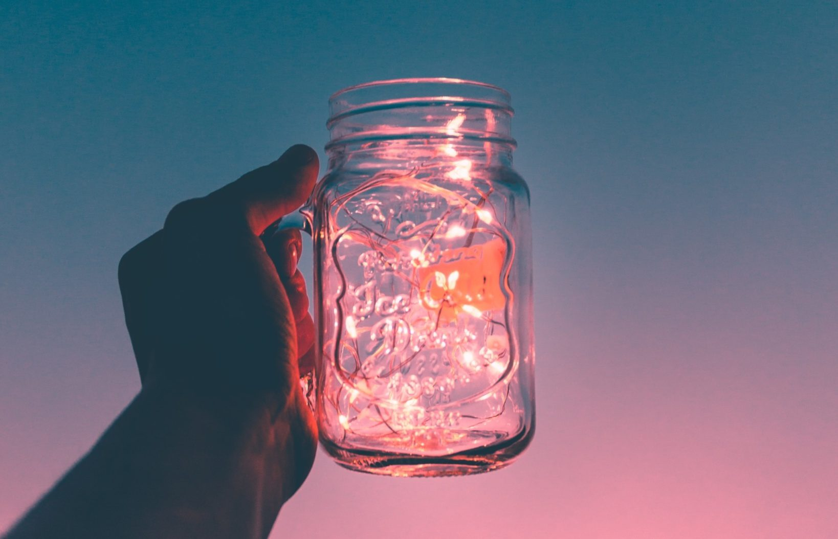 holding glass of water during beautiful sunset
