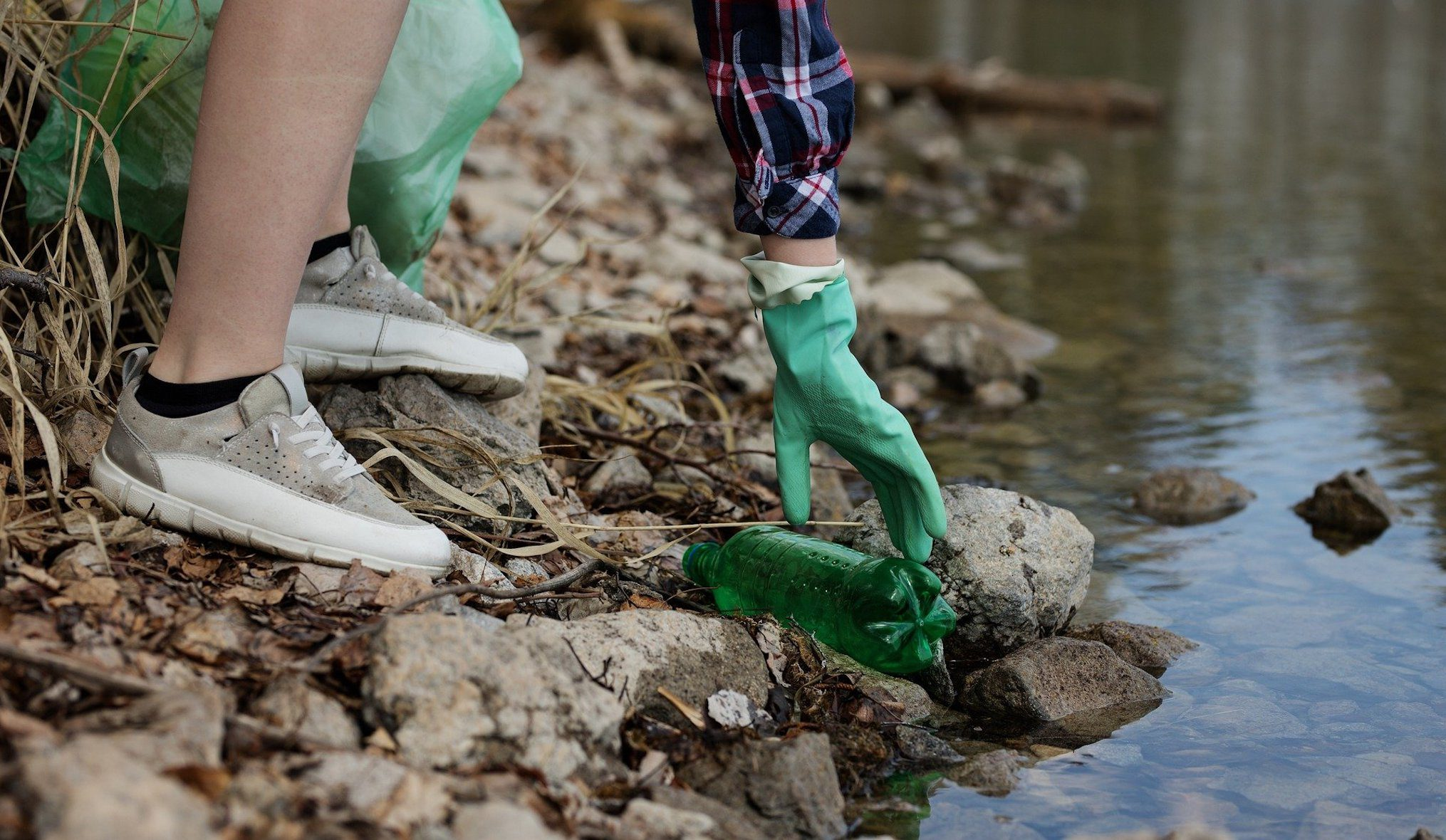 person picking up a single use plastic bottle from a river shore