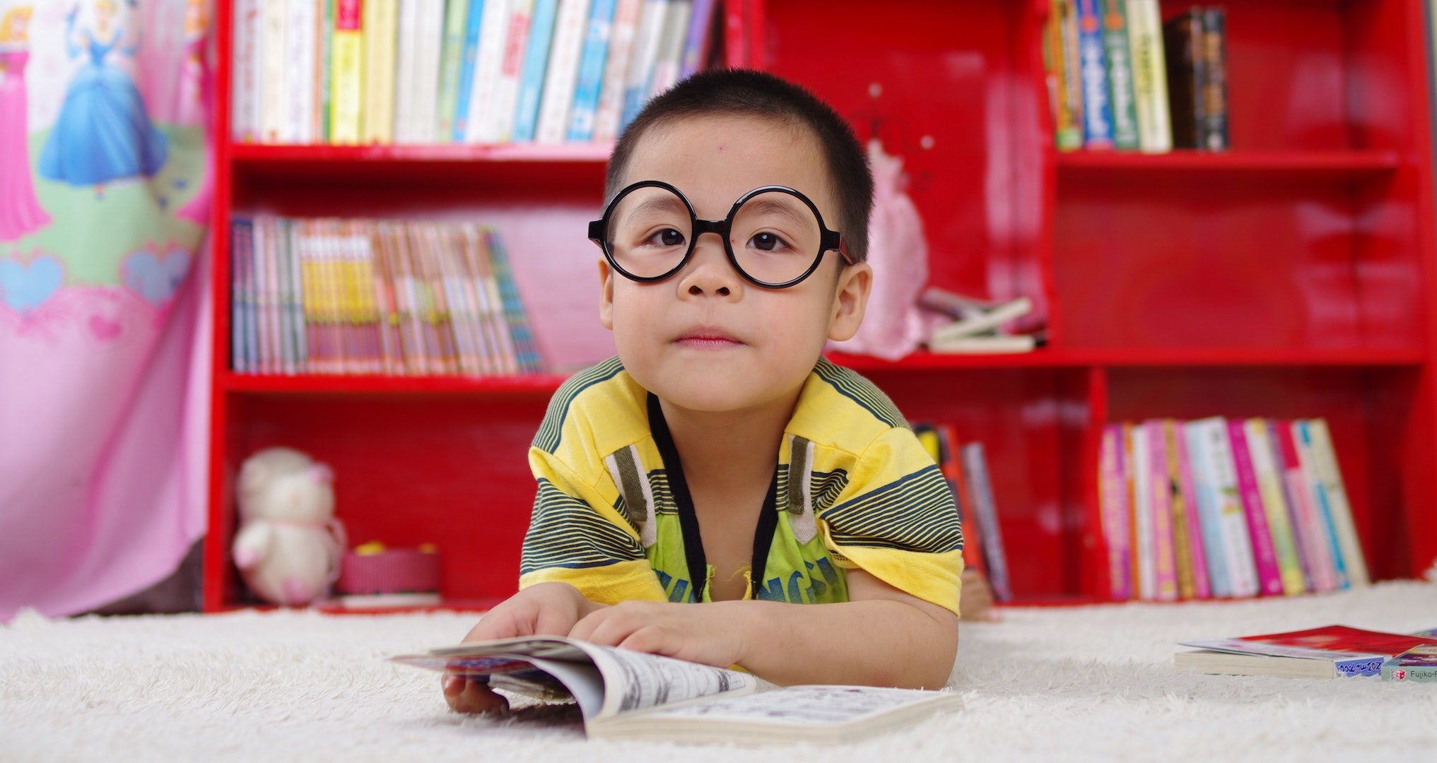 little boy with glasses reading a book in a library